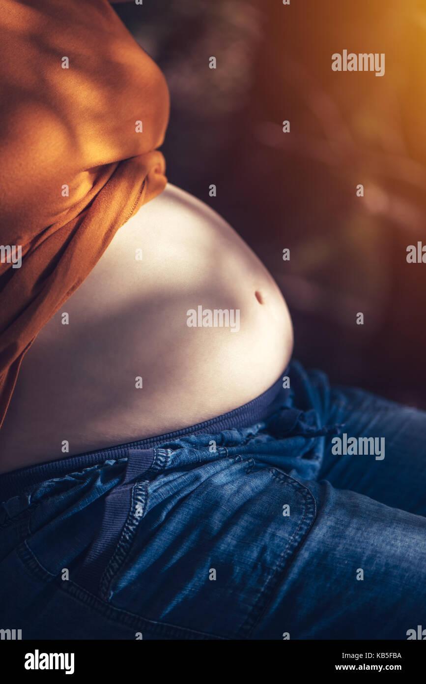 Mujer embarazada vientre relajarse y tomar el sol en el sol caliente del verano, el enfoque selectivo Imagen De Stock