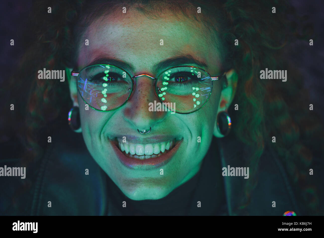 Retrato de una mujer joven por la noche, iluminado con luces de colores Imagen De Stock