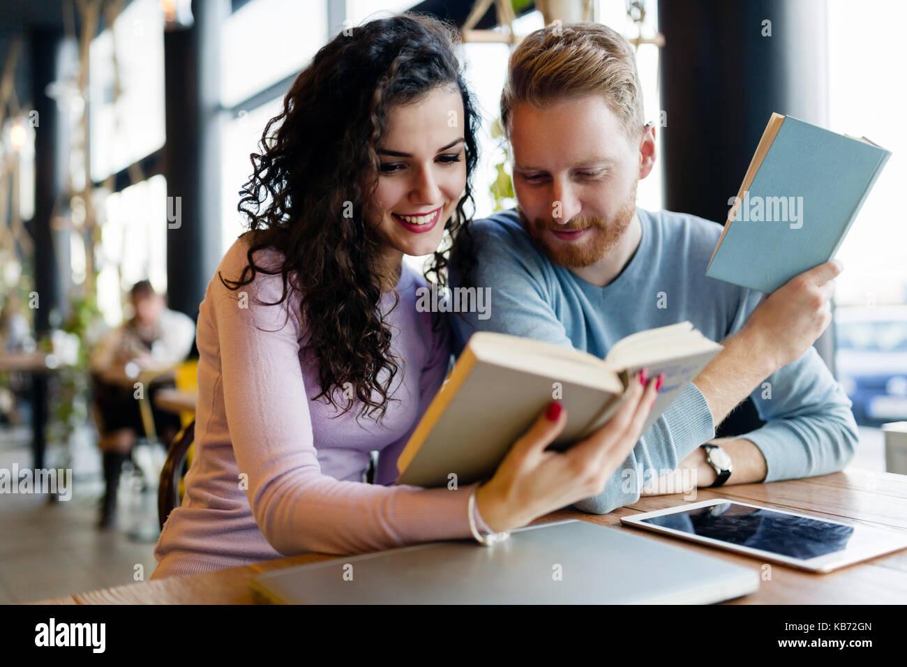 Los jóvenes estudiantes dedicar tiempo a la lectura de libros en la cafetería. Foto de stock