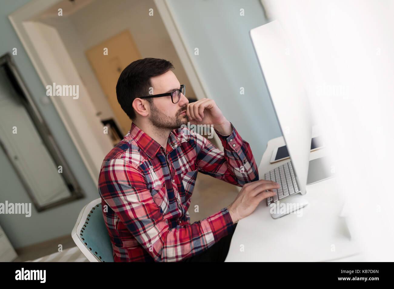 Joven apuesto diseñador que trabaja en el proyecto en el equipo Foto de stock