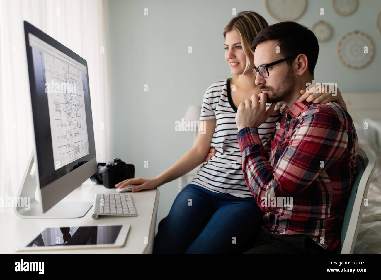 Atractivas jóvenes diseñadores que trabajan juntos desde casa Foto de stock