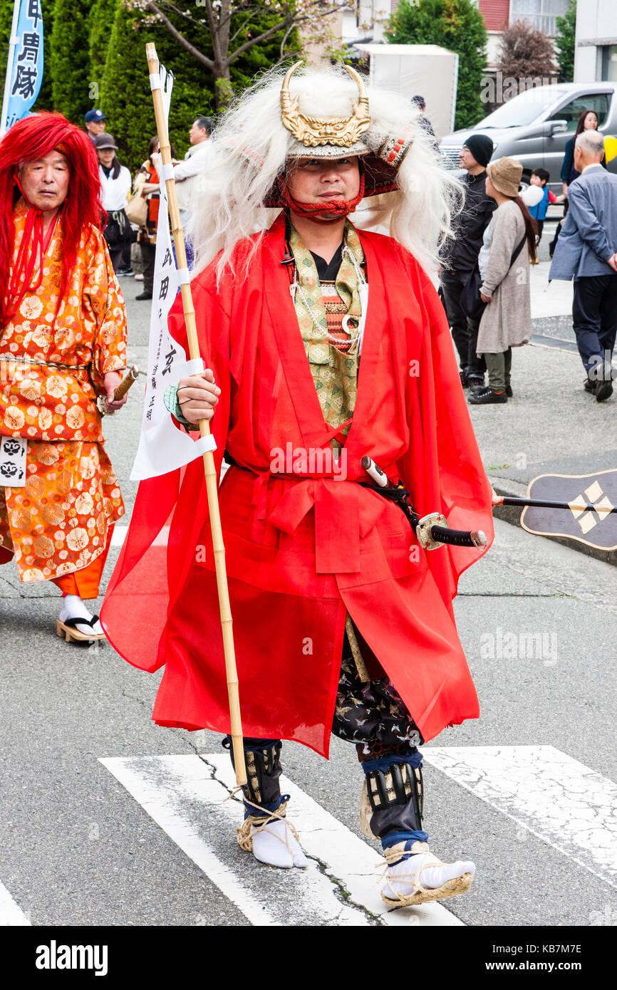 Genji desfile anual en Tada, Japón. Samurai Warrior con abrigo rojo y larga cabellera blanca colgando del yelmo crestado, caminando por la calle. Foto de stock