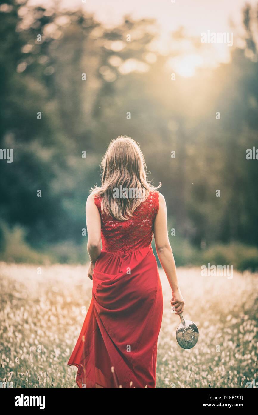 Chica caminando en un campo al atardecer, en un vestido rojo, holdinh un espejo de plata Imagen De Stock