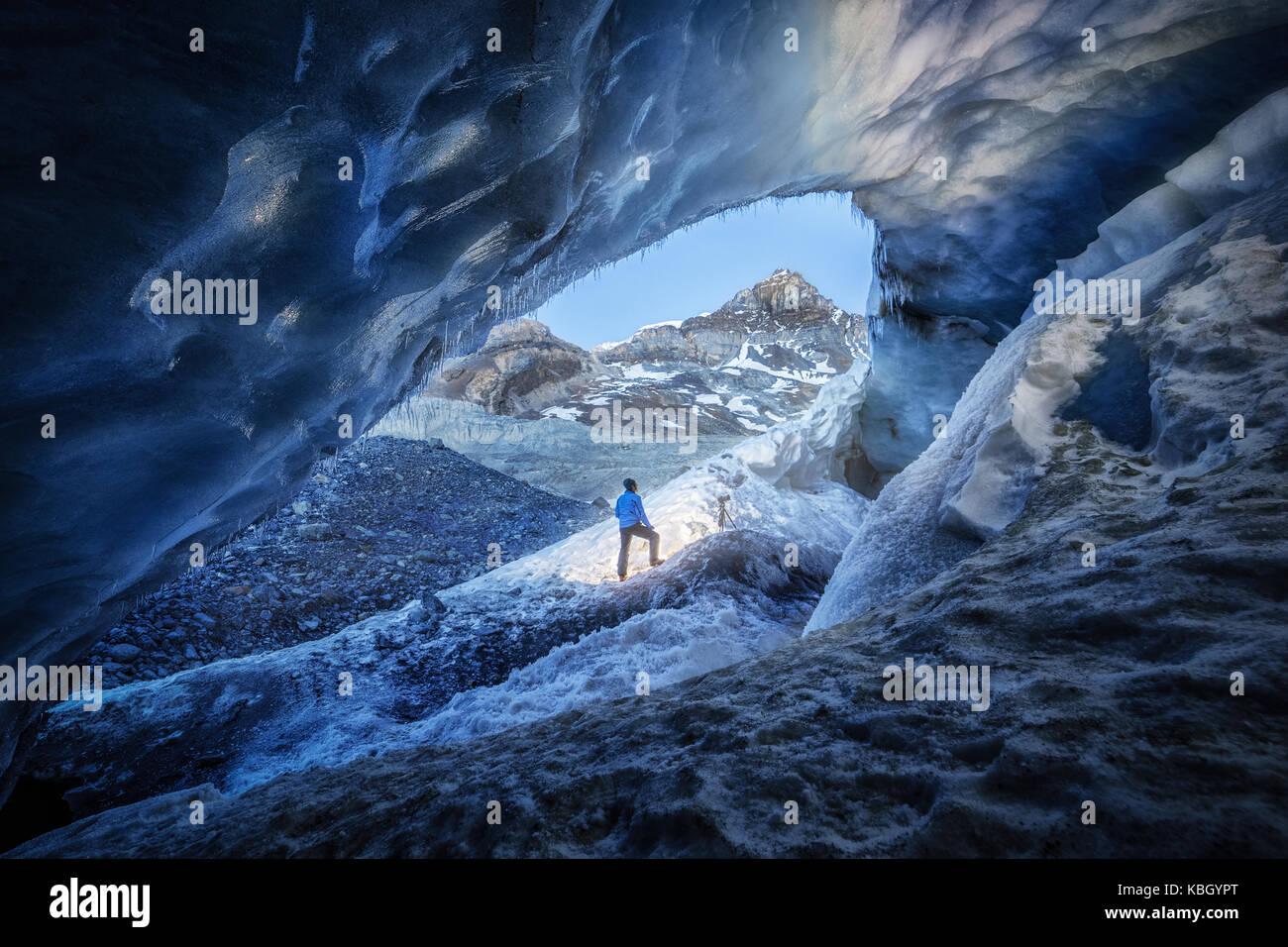 Fotógrafo en el interior de una cueva de hielo durante una expedición de fotografía en el Glaciar Athabasca Foto de stock