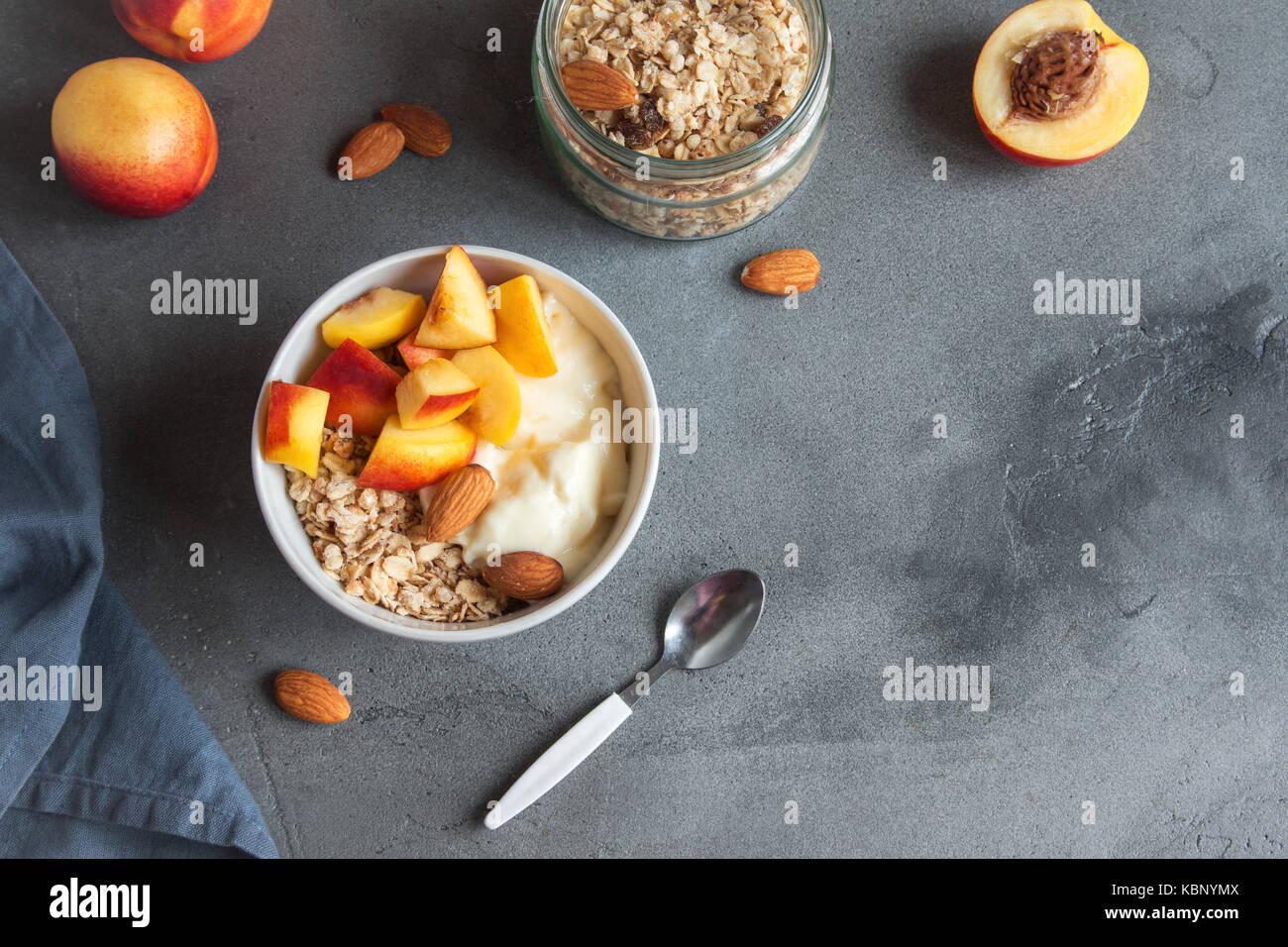 Granola avena casera con yogur y duraznos en un tazón de desayuno saludable. cereales y fruta, tazón de Imagen De Stock