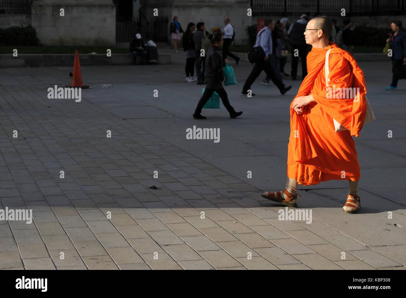 Dos monjes budistas están haciendo turismo en Trafalgar Square, están tomando fotos entre sí. Foto de stock