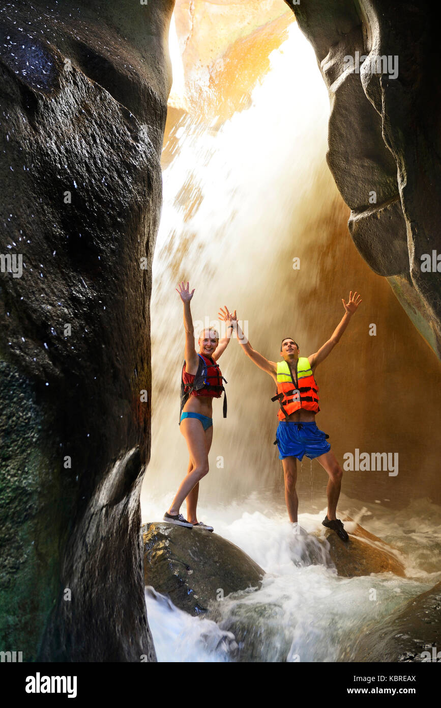 Pareja joven bajo una cascada en el cañón de Wadi Mujib, Jordania Imagen De Stock