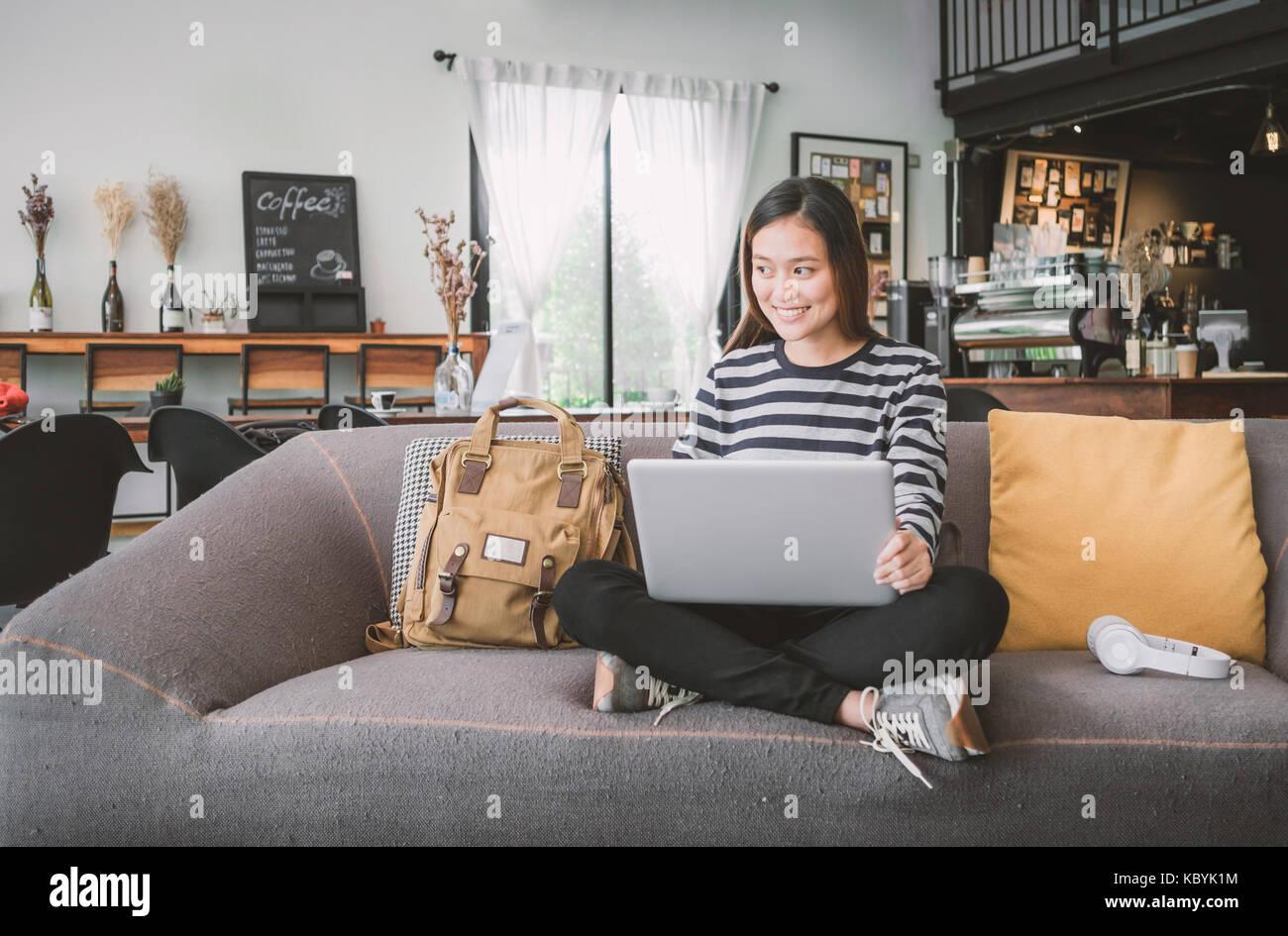 Joven asiática con ordenador portátil y escuchar música en el sofá con cara sonriente, feliz en la cafetería,edad Foto de stock