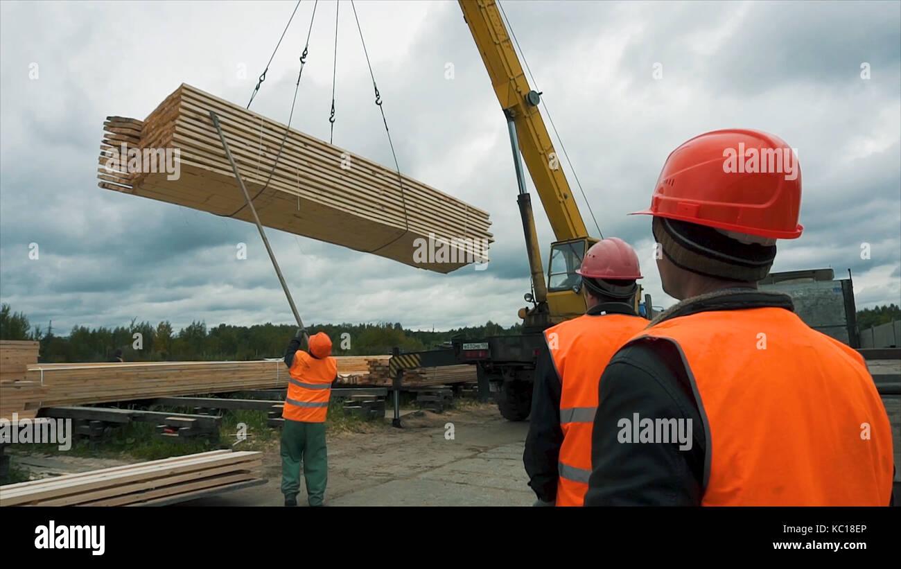 Los trabajadores transportando una barras de madera con una grúa ...
