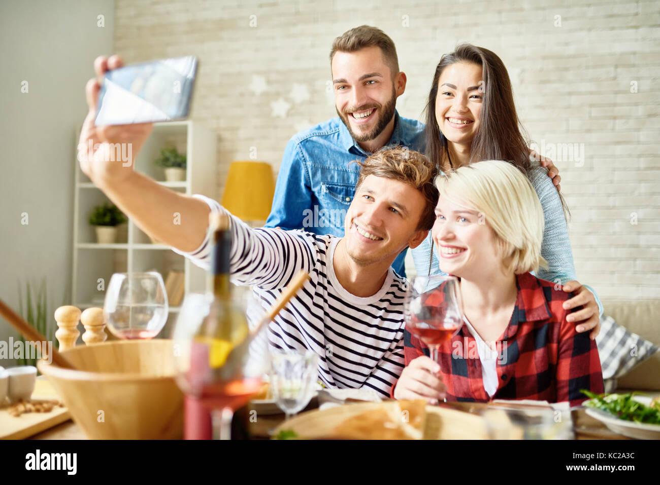 Retrato de cuatro amigos tomando selfie feliz en la mesa mientras celebraba la fiesta juntos Imagen De Stock