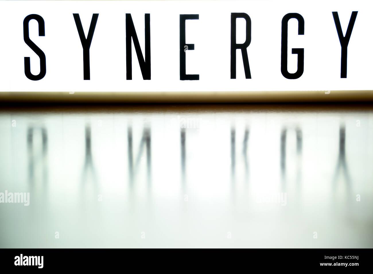 Una junta de luz muestra la frase sinergia en madera Imagen De Stock