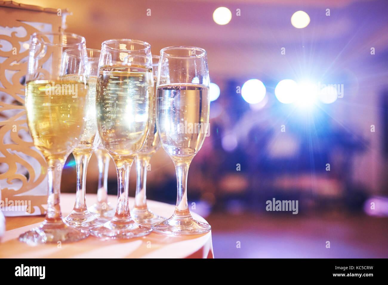 Un montón de copas de vino en la luz azul con un fresco delicioso vino blanco o champán en el bar Imagen De Stock