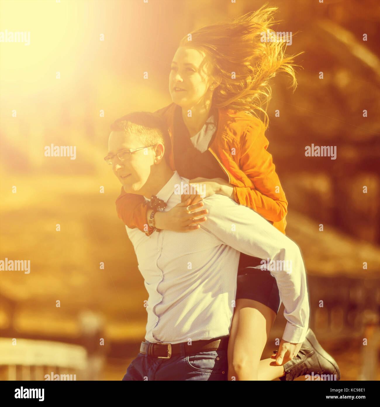 Feliz el hombre lleva a su novia en la parte posterior del puente sobre el río tono vintage. Imagen De Stock