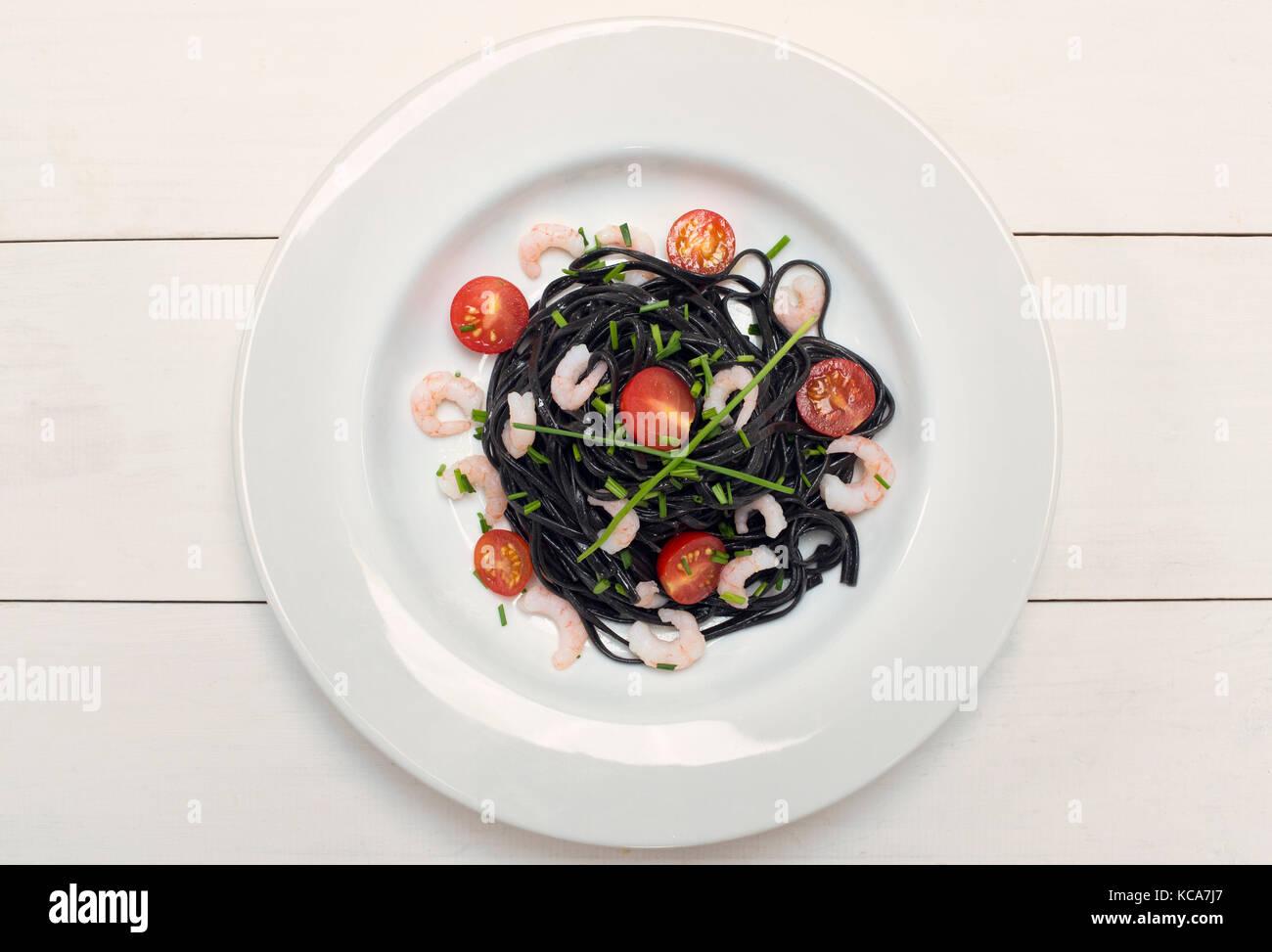 Tinta de calamar negro Pasta con langostinos, anchoas y tomates sobre un fondo blanco. Foto de stock