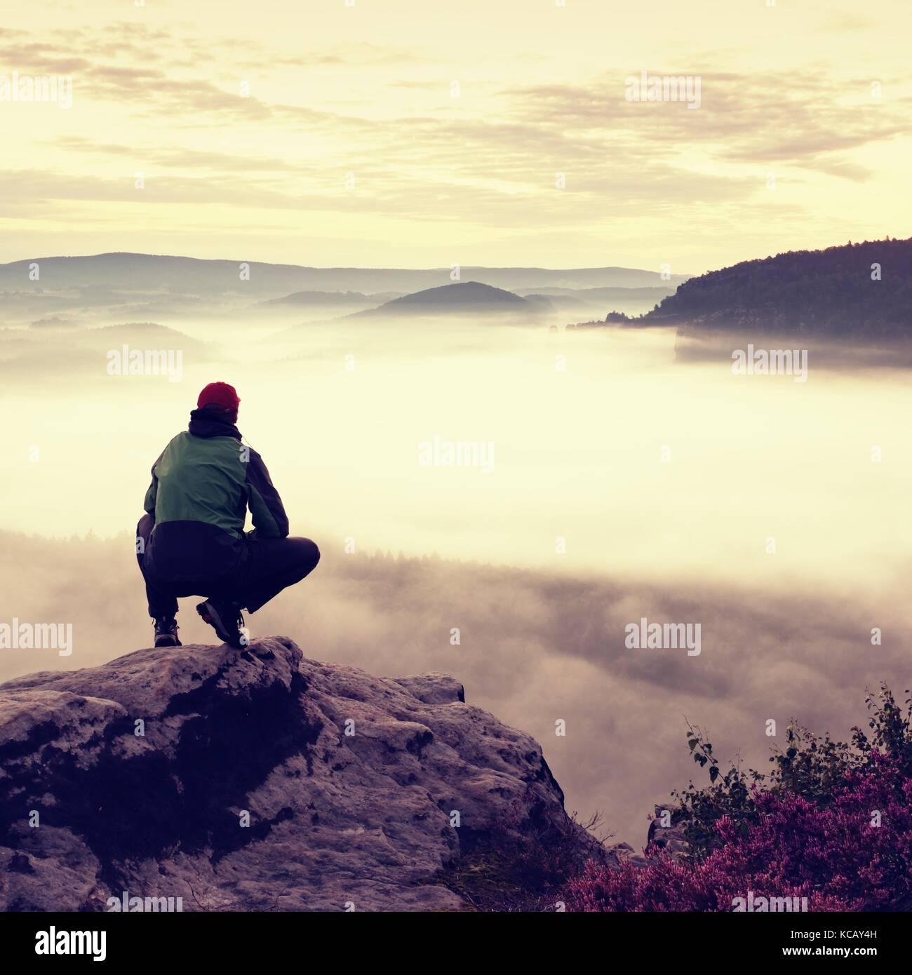 Turista en tapa roja y verde negro sportswear en cuclillas sobre una roca, disfrutar el paisaje del otoño Imagen De Stock