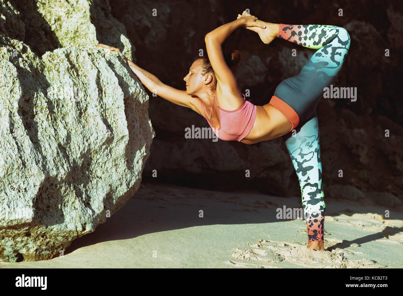 Meditación sobre la roca de fondo. joven mujer activa de pie en pose de yoga en la playa rock, estiramiento Imagen De Stock