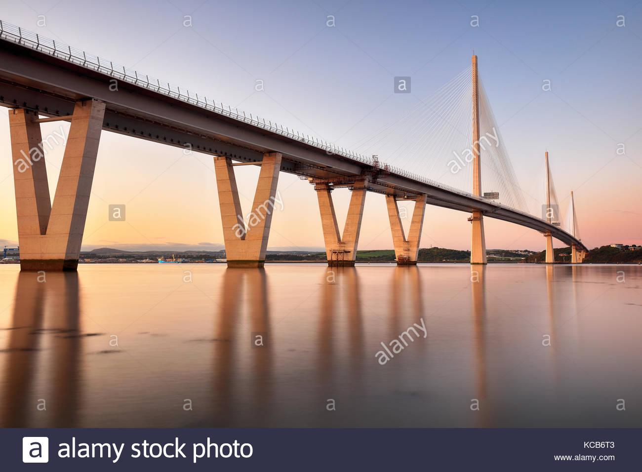 Reflexiones de la nueva Queensferry cruzando el puente sobre el Firth of Forth durante la puesta de sol. Foto de stock