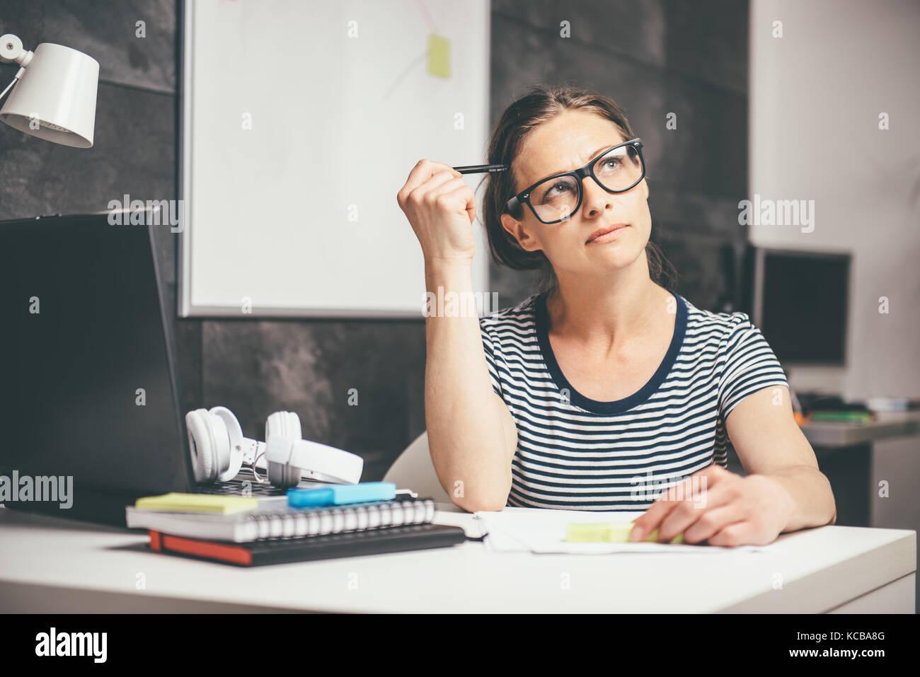 Mujer vistiendo gafas escribir notas y contemplando en la oficina Imagen De Stock
