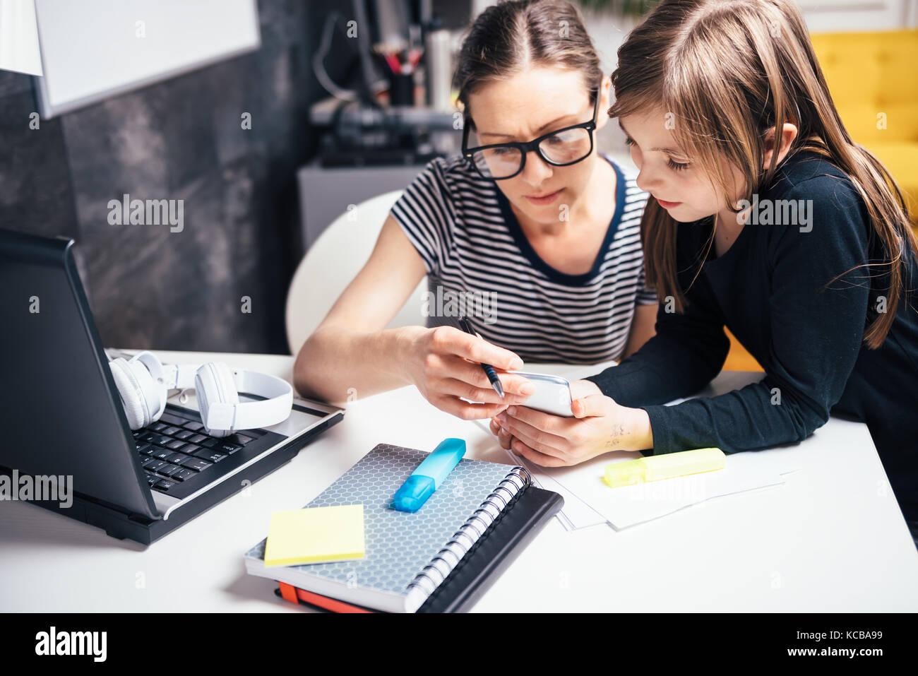 Madre e hija utilizando el teléfono inteligente en la oficina principal Imagen De Stock