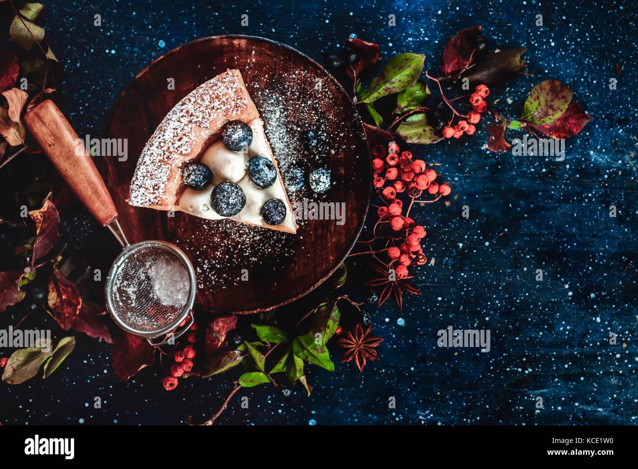 Close-up de un pedazo de pastel de calabaza con azúcar en polvo y un tamiz en placas de madera. platos elaborados Imagen De Stock