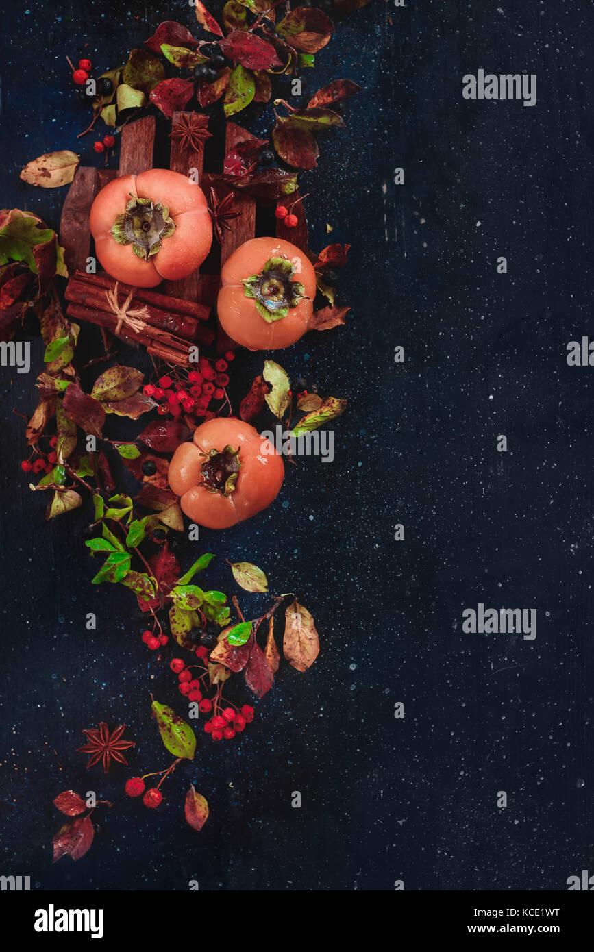 Caquis maduros sobre un fondo de madera oscura con hojas de otoño, bayas y canela. plano sentar con espacio Imagen De Stock