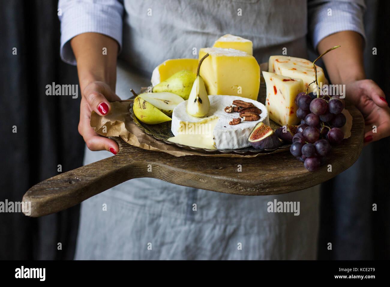 Mujer joven sosteniendo un plato de queso en el tablero de madera Imagen De Stock
