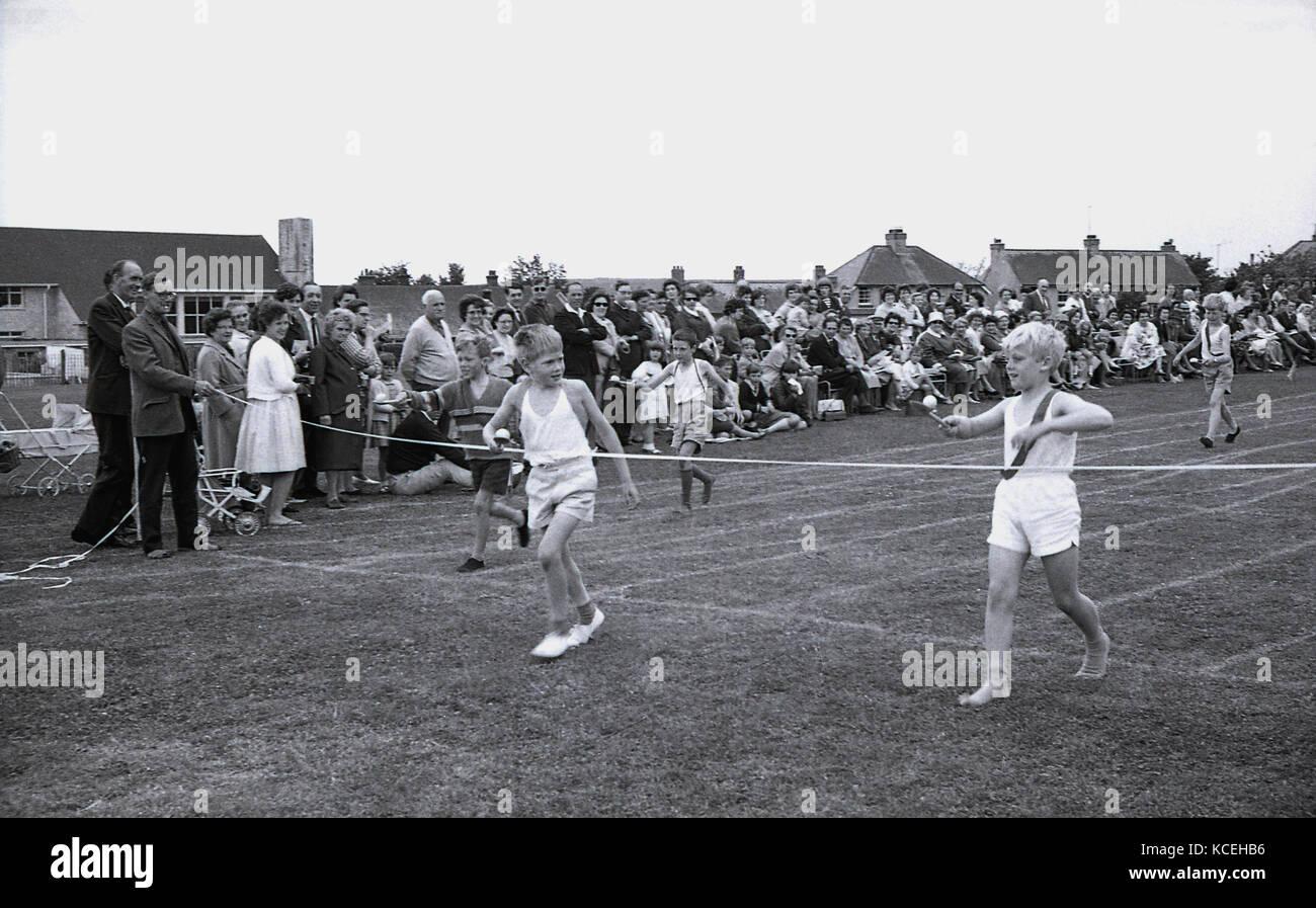 1960, históricos, los muchachos compiten en un huevo y cuchara en la carrera de un día de deportes de Imagen De Stock