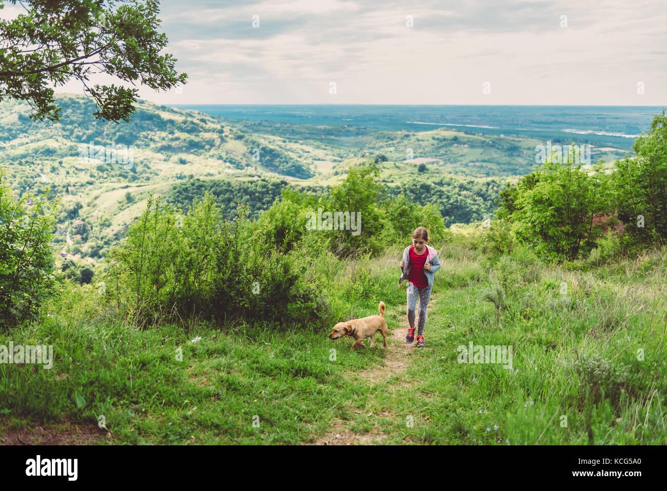 Chica y su perro caminando por un sendero de trekking Imagen De Stock