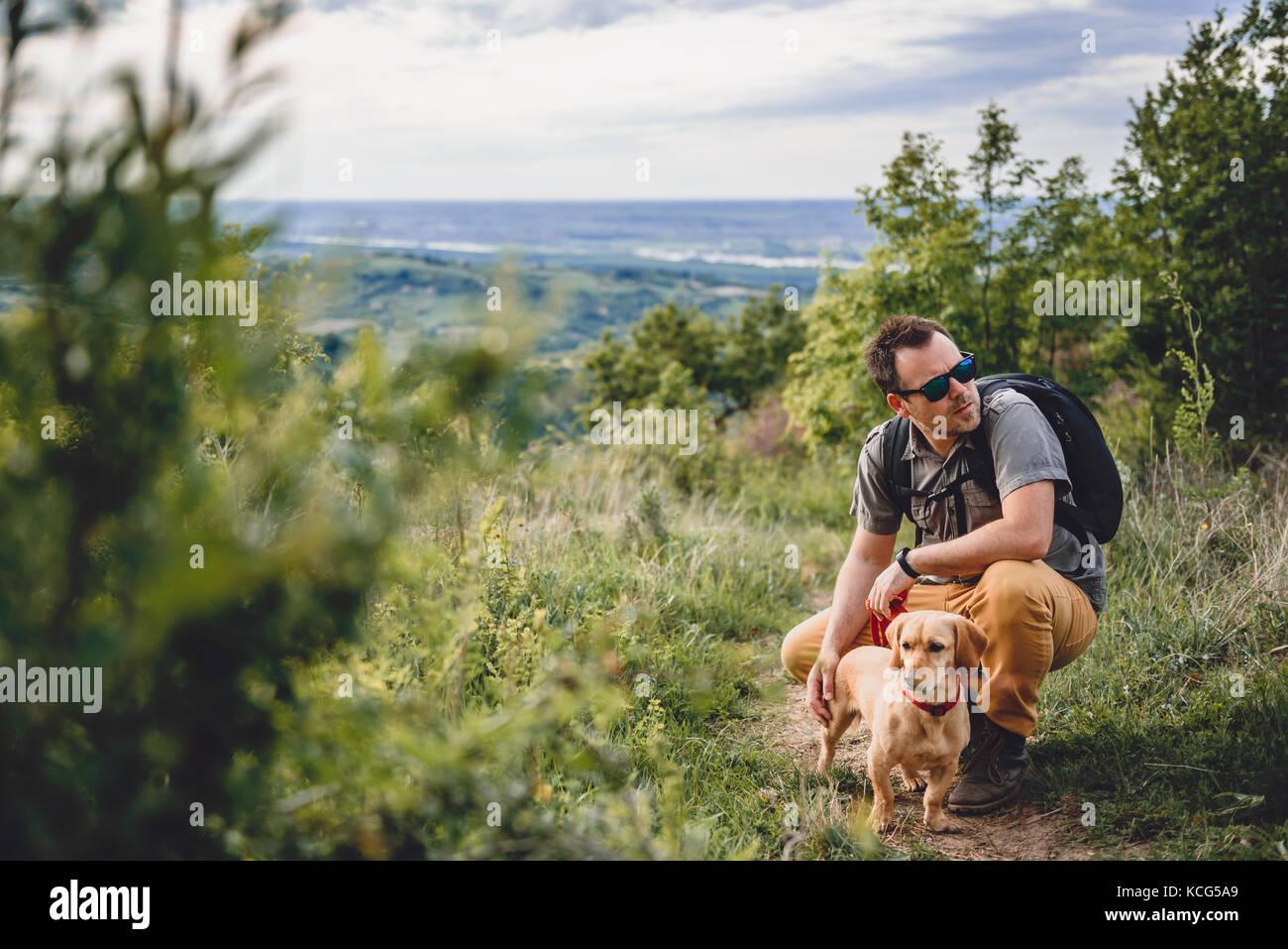 Hombre con gafas de sol con un pequeño perro amarillo descansando en el sendero de trekking Imagen De Stock