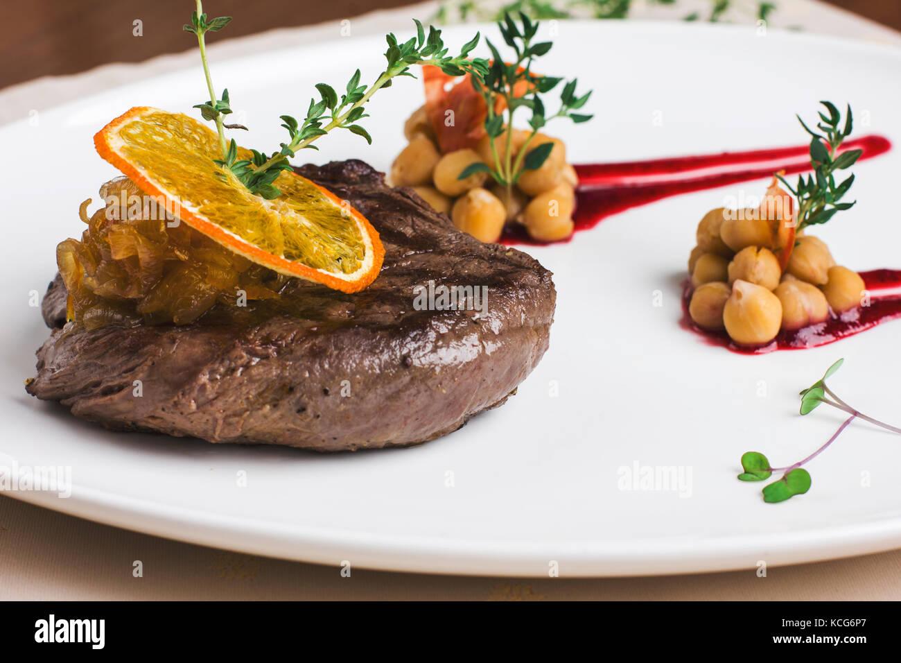Jugoso filete de ternera con salsa de naranja con verduras y garbanzos Imagen De Stock