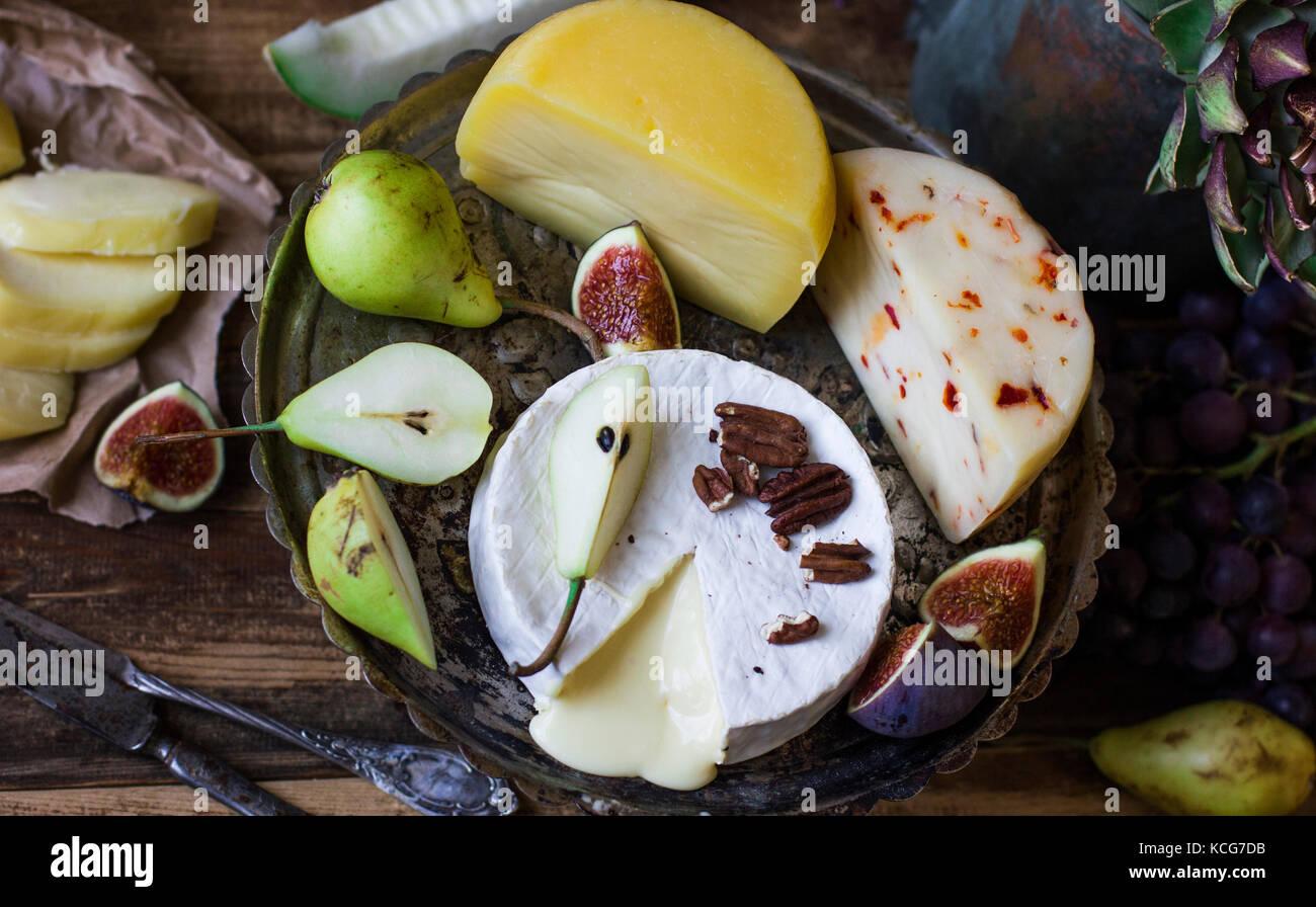 Los distintos quesos y fruta fresca en el fondo de madera Imagen De Stock