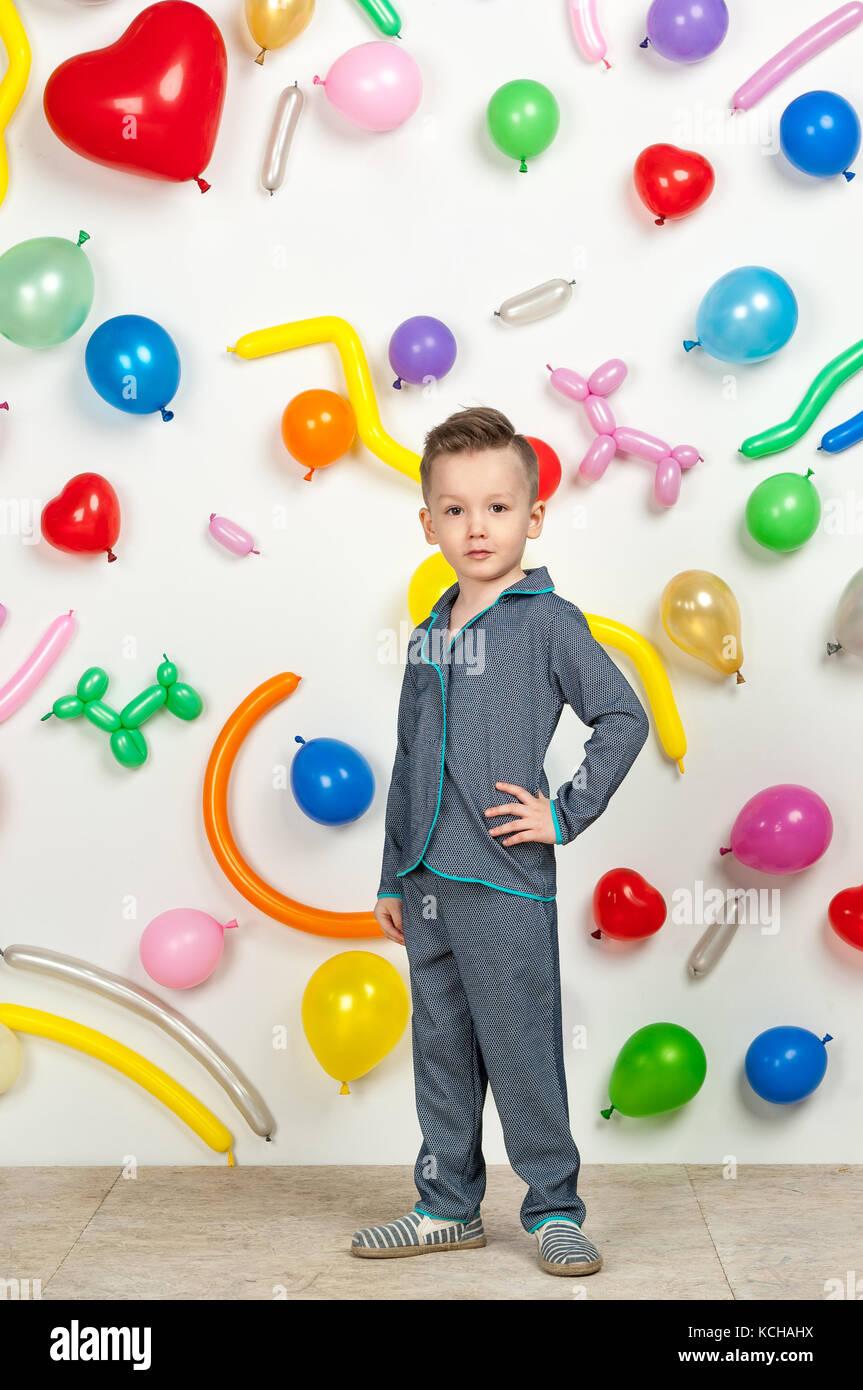 564b674be1 Niño sobre un fondo blanco con globos de colores. chico en pijama sobre un  fondo