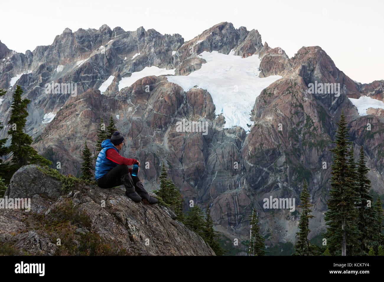 Un solitario caminante en busca del séptimo/rousseau macizo y su ventisquero colgante en el camping de la noche Imagen De Stock