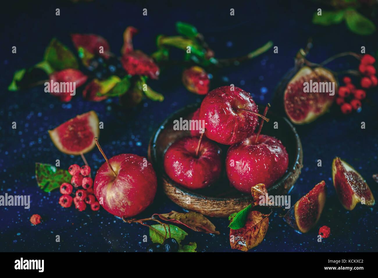 Maduras manzanas dulces en una placa de madera cerca de un otoño bodegón con hojas caídas. cosecha Imagen De Stock