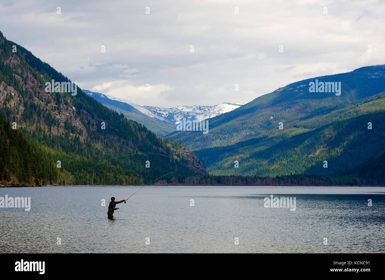 Joven de la pesca con mosca en el lago cerca de lumby Mabel en la región de Okanagan de la Columbia Británica, Imagen De Stock