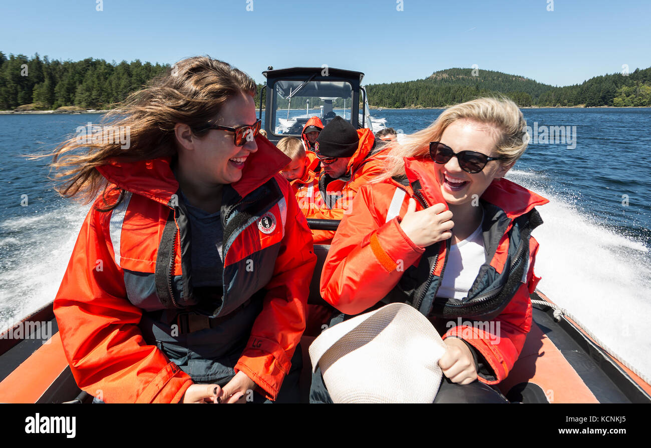 Dos amigos toman en la experiencia de un viaje de avistamiento de ballenas desde el frente de la zodiak justo al Imagen De Stock