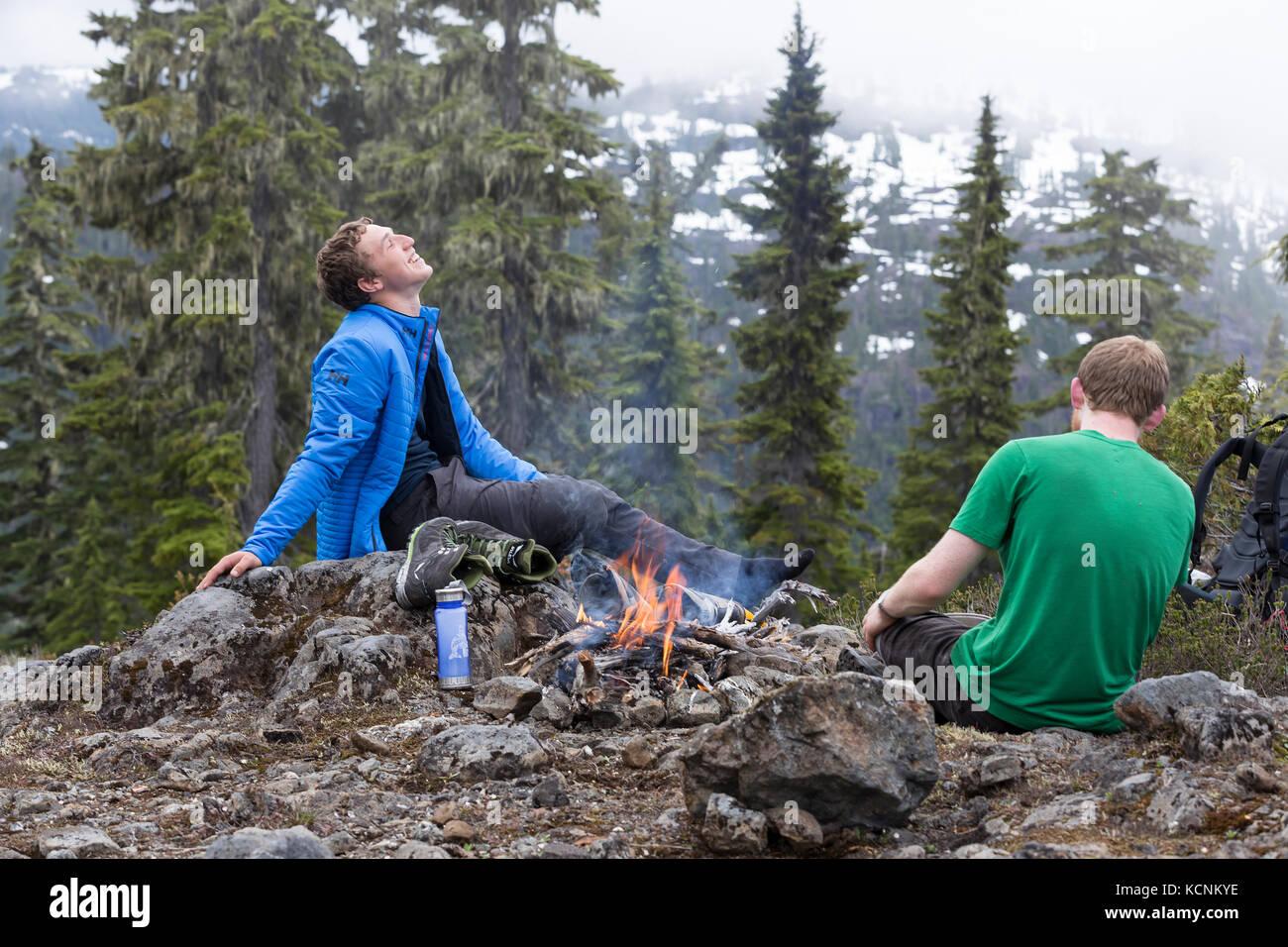 Dos amigos comparten una risa en un fuego de campamento mientras senderismo en lee meseta. La isla de Vancouver, Imagen De Stock