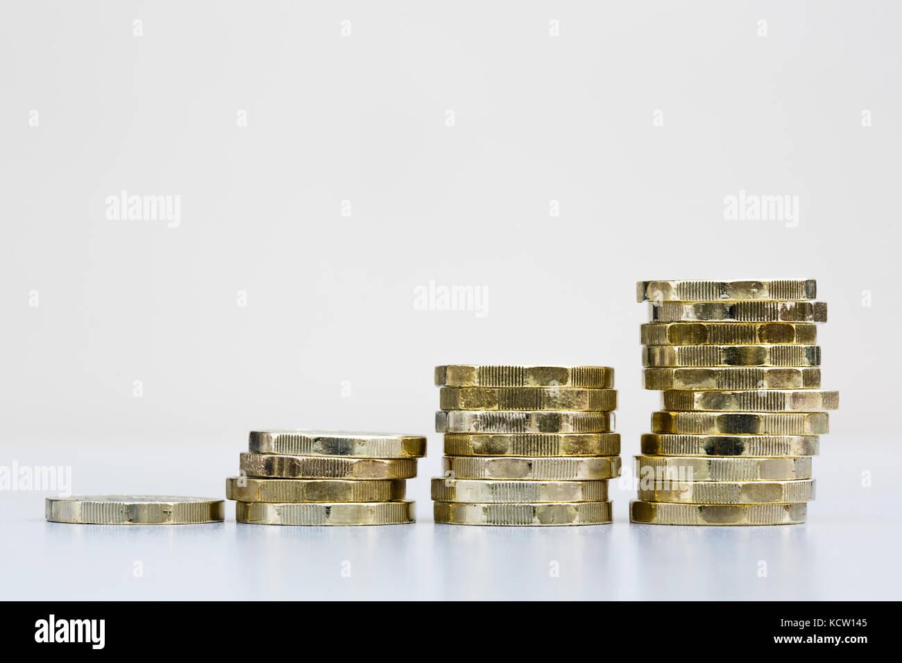 Montón de dinero británico libras esterlinas nuevas monedas de una libra dinero en efectivo GBP en cuatro pilas Ahorra ahorros crecimiento crecimiento concepto de crecimiento financiero Inglaterra Reino Unido Gran Bretaña Foto de stock