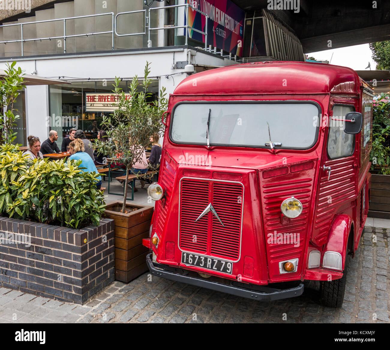 Un vintage Citroën H panel van pintadas de rojo y aparcamos fuera un bar / restaurante en el South Bank de Londres, Inglaterra, Reino Unido. Foto de stock