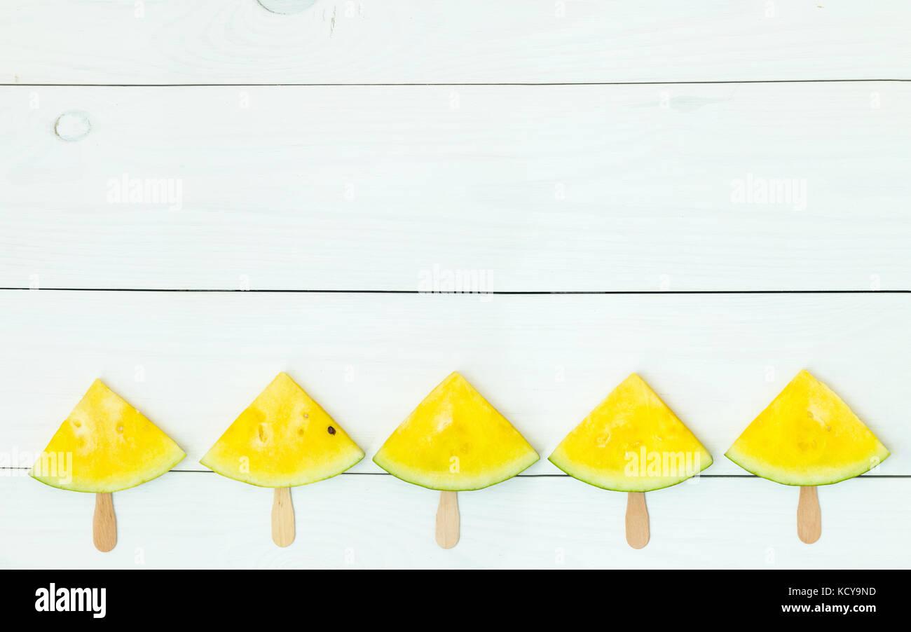 Rebanadas de sandía amarilla brillante sobre palos de madera sobre un fondo de madera blanca. plano laico, Imagen De Stock