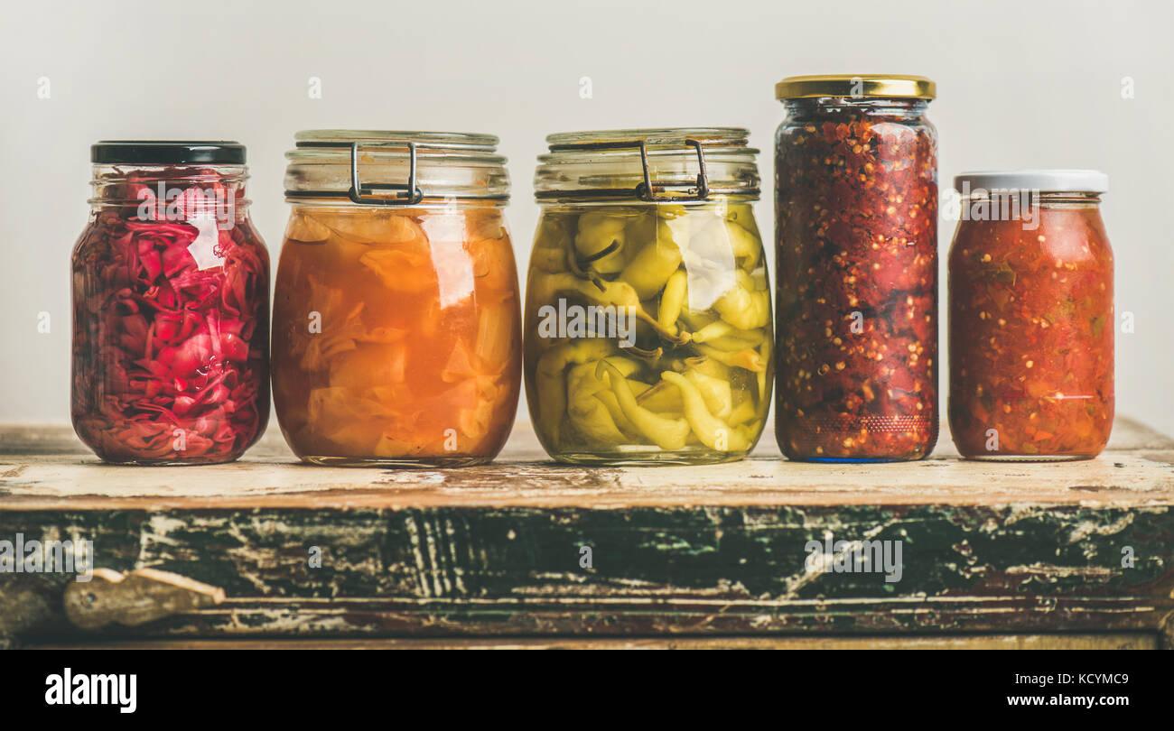 Otoño colorido encurtido de vegetales en frascos colocados en línea Foto de stock