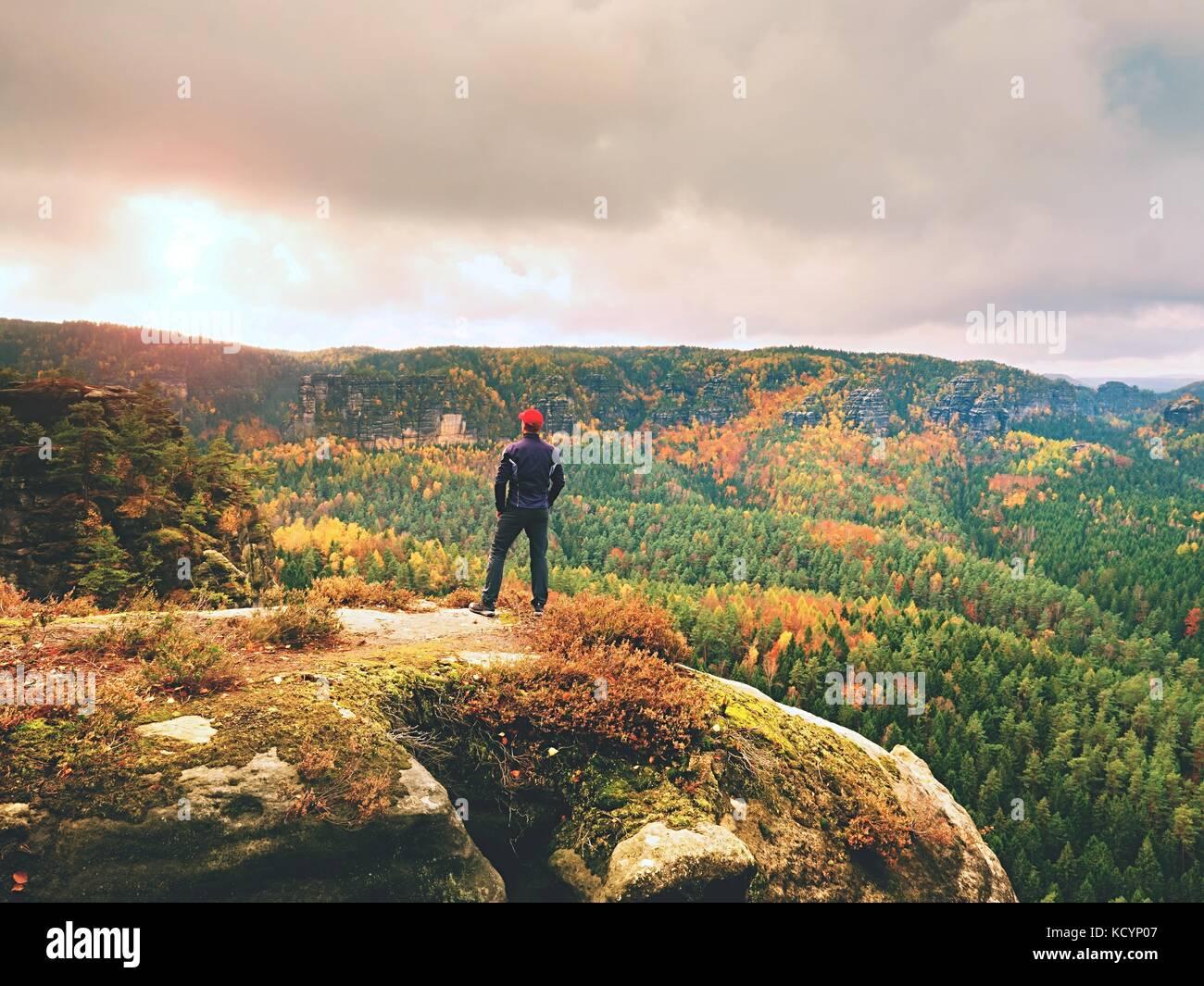 Solo turista con piscina deportiva y la mochila de pie en borde del acantilado y viendo en otoño colorido valle Imagen De Stock