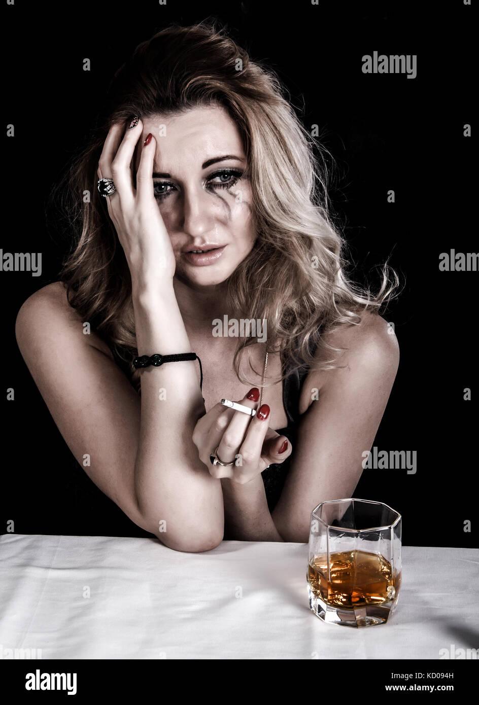 Pisado joven con un vaso de whisky y un cigarrillo sobre fondo negro Imagen De Stock