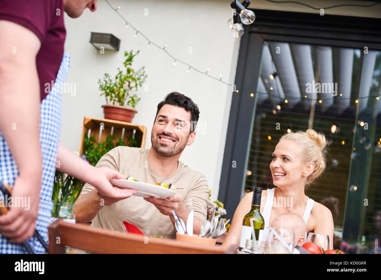 El hombre entrega la placa a la par con la hija de la familia a comer en el patio Imagen De Stock