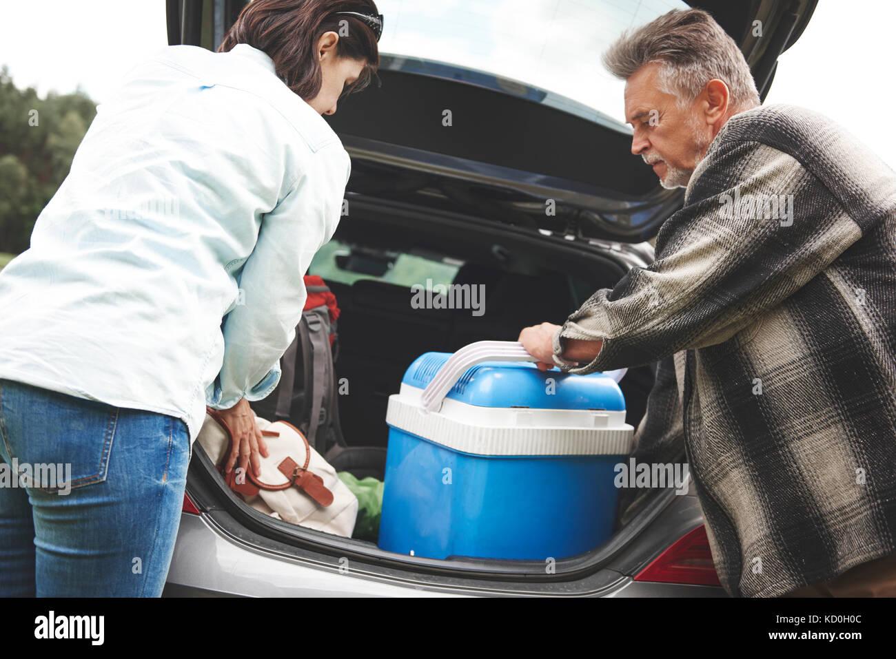 Pareja mayor extracción de equipo de camping en el maletero del coche Imagen De Stock