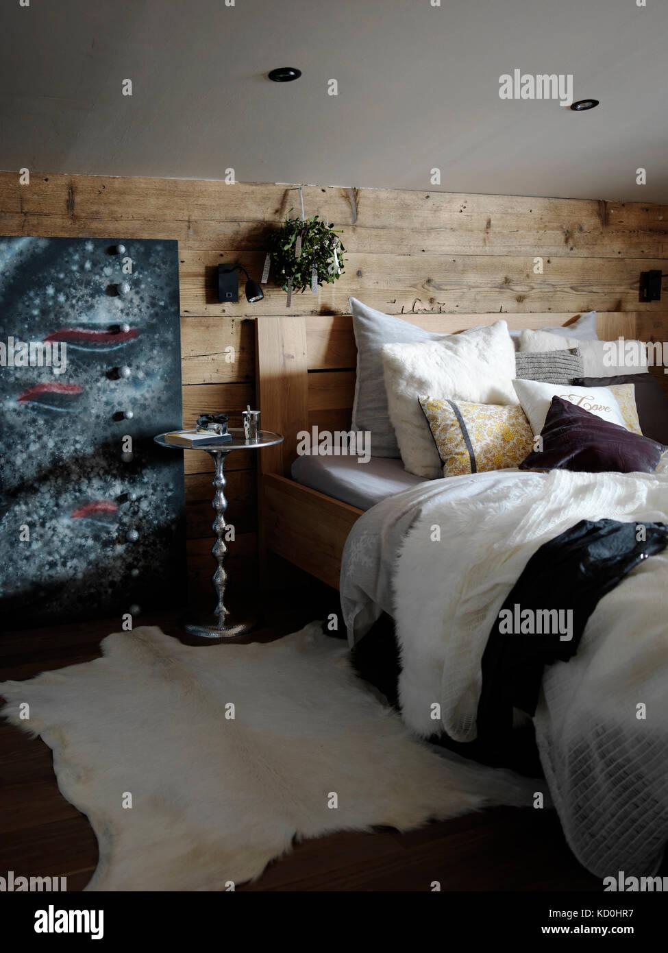Interior del dormitorio, cubierto de madera pared detrás de la cama Foto de stock