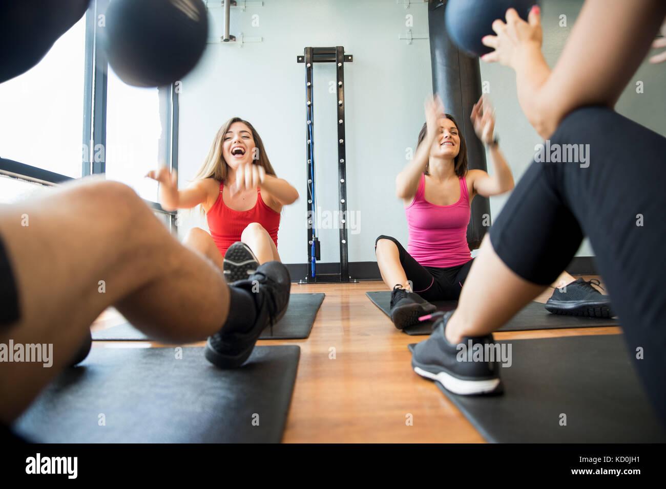 Amigos entrenamiento con balón medicinal en el gimnasio Imagen De Stock