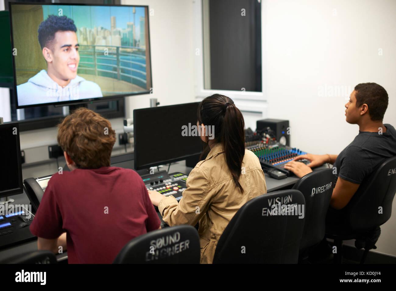 Jóvenes varones y mujeres estudiantes universitarios en mesa de mezclas viendo la pantalla del televisor Foto de stock