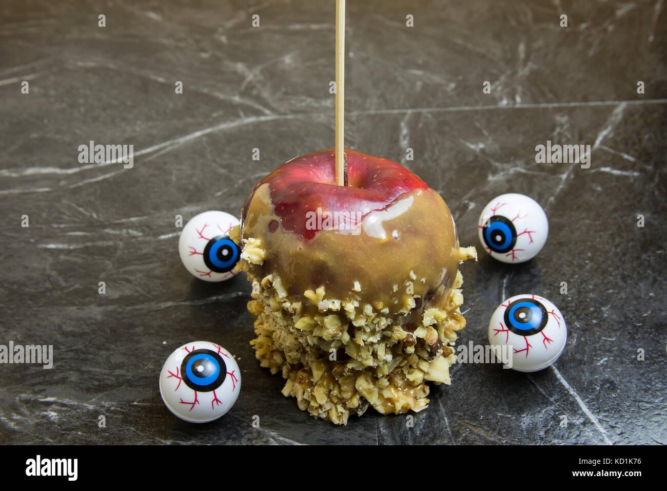 Luces rojas manzanas de caramelo recubierto con nueces picadas, rodeado por los globos oculares. Imagen De Stock