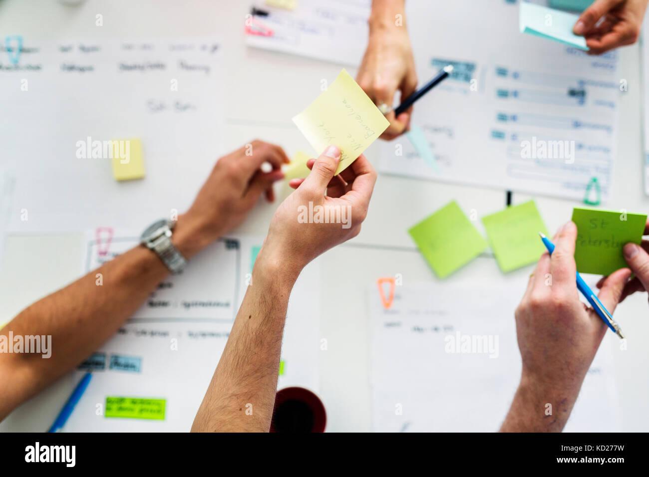 Compañeros mediante notas adhesivas durante la reunión de negocios Imagen De Stock